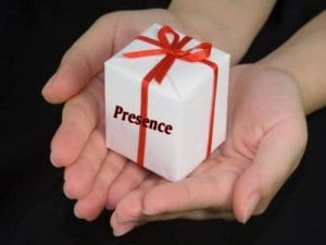 "Two hands holding a gift which says ""Presence"""